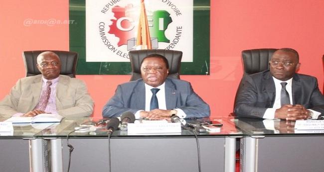 le président de la CEI assis entre deux collaborateurs